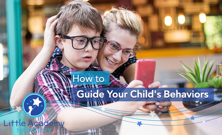 A child wearing glasses and holding a mobile phone in his both hands and behind him there is his mother and is putting a hand on his head and holding the cell phone with other hand