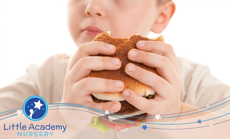 A boy is holding ham burger in his both hands and took a first bite of it
