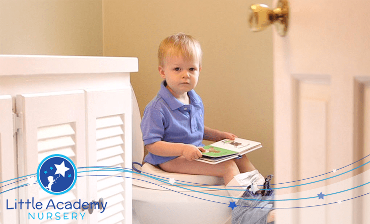 A kid wearing blue shirt and white pants is sitting on the washroom commode is holding a book in his hands