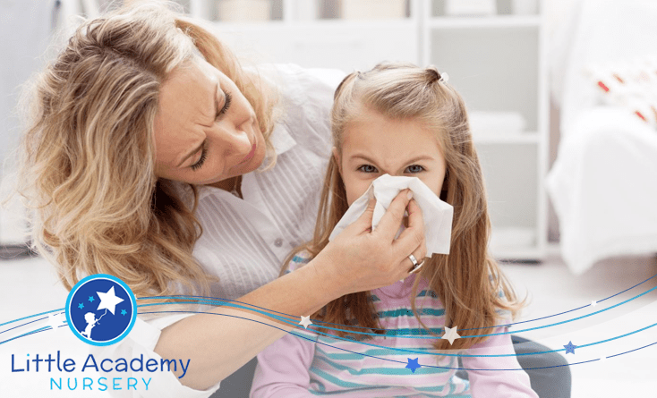 A kid is blowing her nose over the tisse the mother is putting over her nose. the kid is wearing pink and white dress and the mother is wearing white on the right of the kid