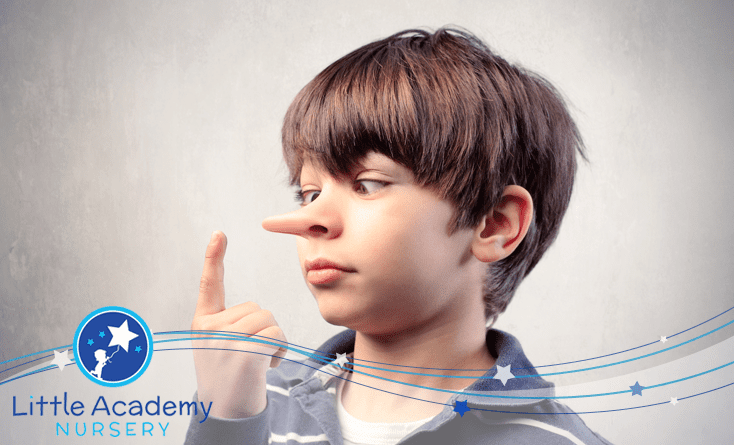 A child is pointing his right hand's finger towards his nose