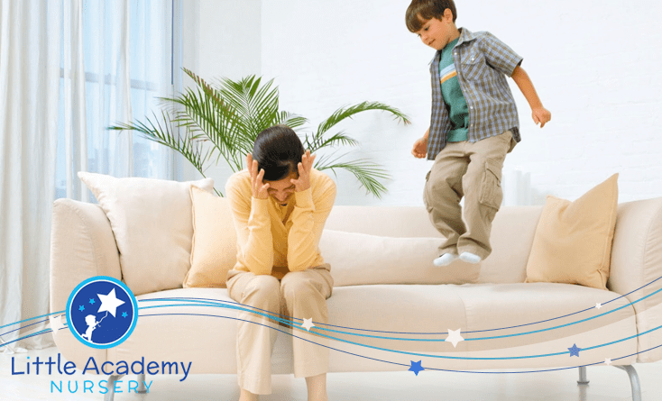 A kid on the right is jumping on the sofa and a lady is putting her hands on her head and is sitting on the sofa