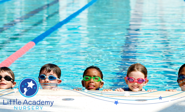 five kids wearing swimming goggle over their eyes are swimming in a pool and their heads are visible form the water