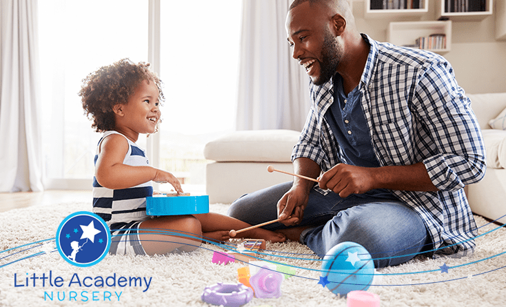 A child and a man are sitting in front of each other and both are doing some activity with toys.