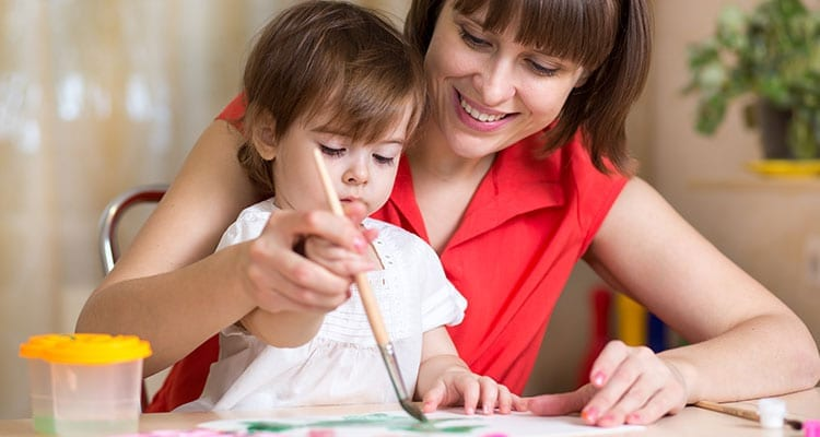 a woman who is wearing red dress is helping a small kid, which is wearing a white shirt. in writing her home work.