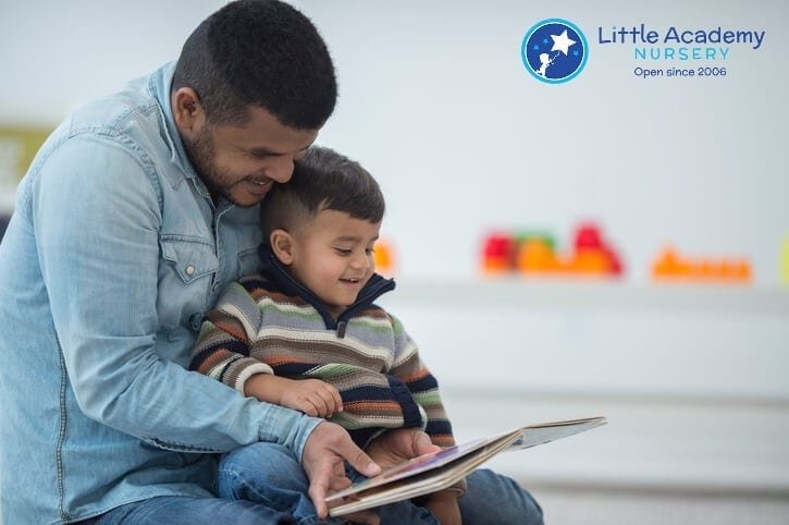 Man wearing blue shirt and blue jeans is holding a boy is his arms and reading from a book.