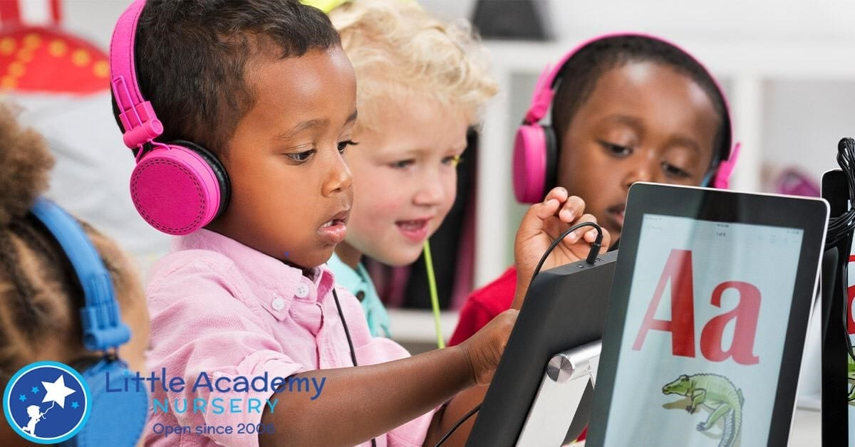 group of small kids wearing headphones in their ears, and trying to read alphabetical book