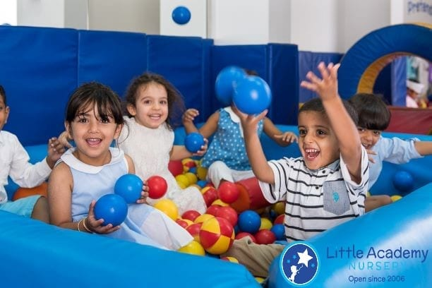 A group of kids playing with round shape blue, red and yellow balls.