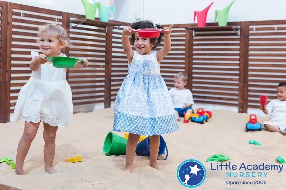 A girls wearing sky blue and white dress are playing and behind them there are more kids which are playing with different toys.