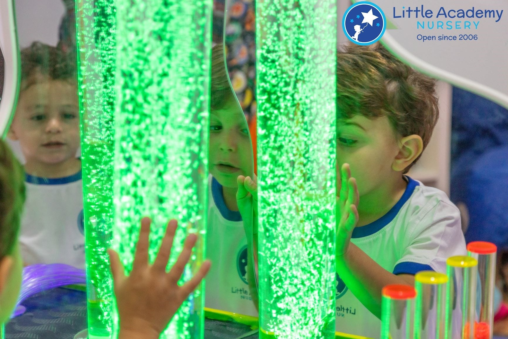 A group of students are doing activity in a sensory room. They are touching a sensory play device.