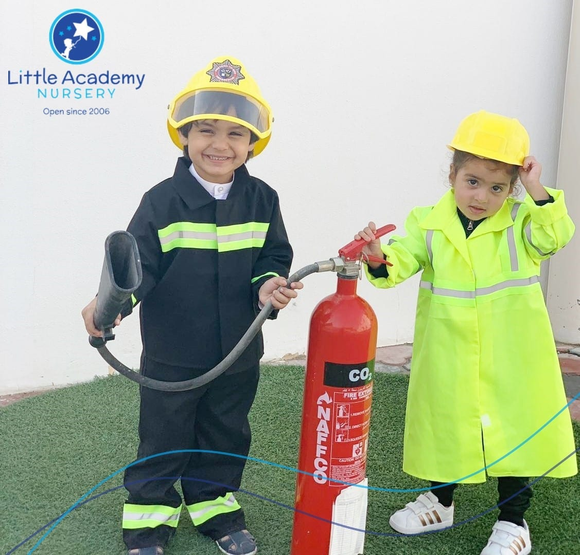 Two boys holding a fire drill are standing side by side. they are wearing black and yellow dress.