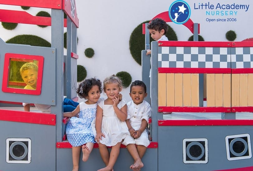 A group of little girls are playing over a toy. They are wearing white and blue dress.