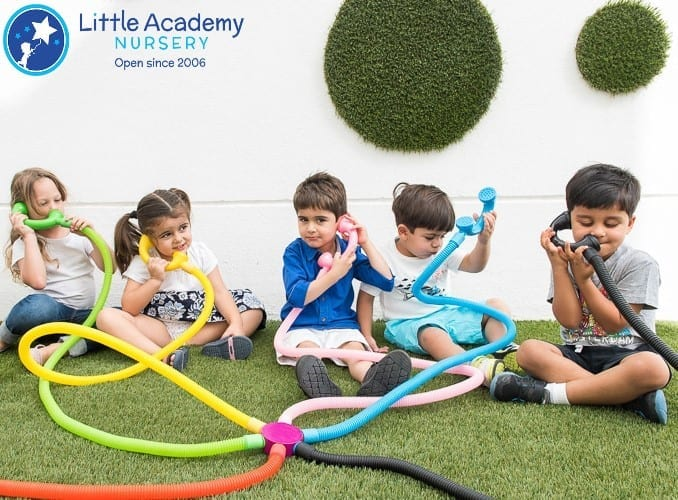 A group of children, three boys and one girl wearing blue , grey, white and pink dress are trying to communicate with each other through communication pipe device.
