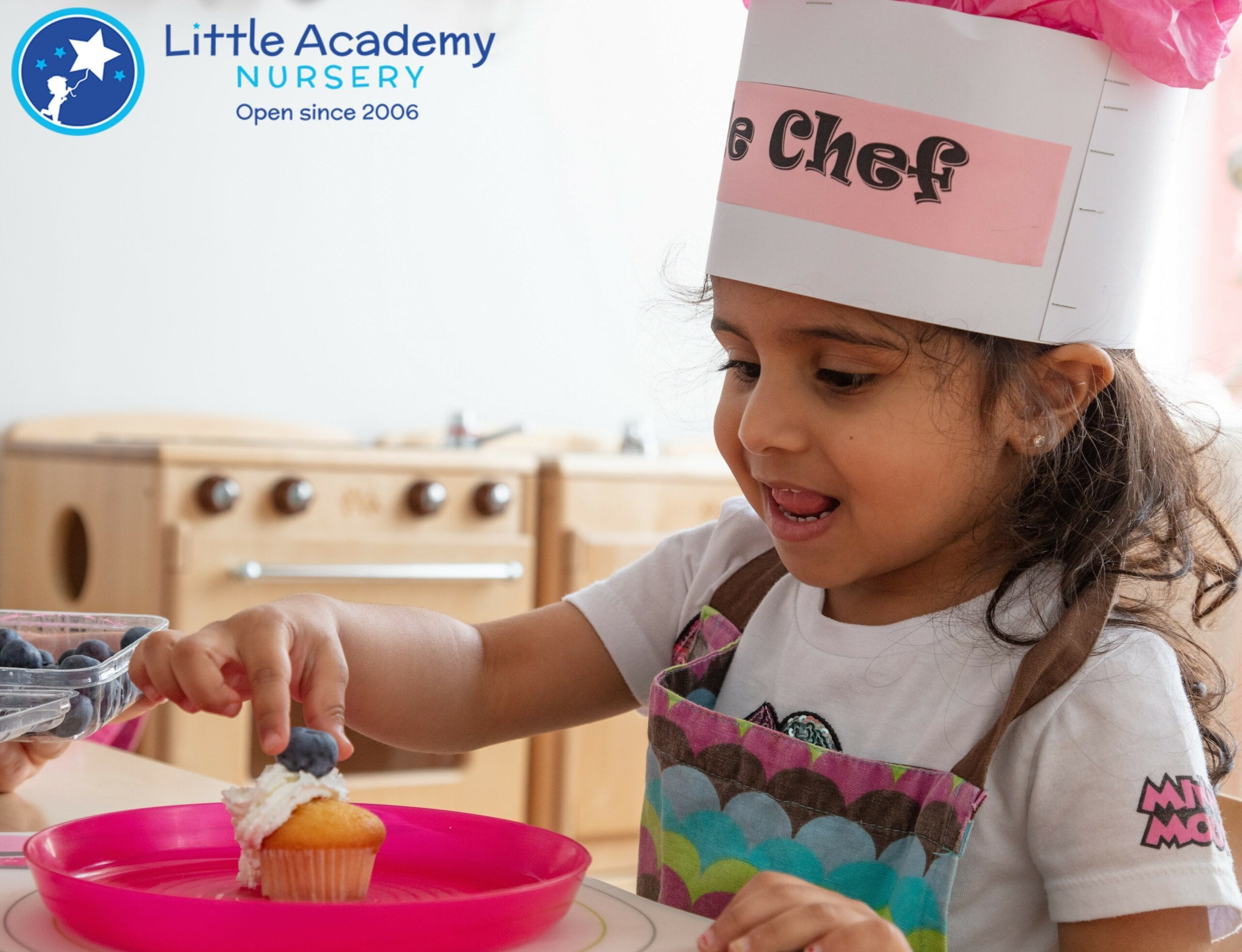A Girl wearing a cooking hat on her head and picking up a piece of cake in her right hand.