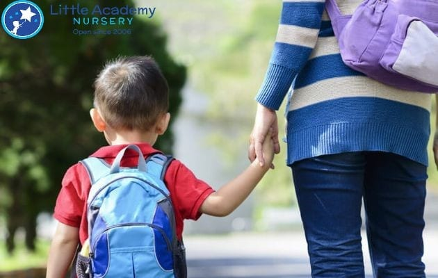 A little kid wearing a blue bag and red shirt hold a woman's hand on the right of him.
