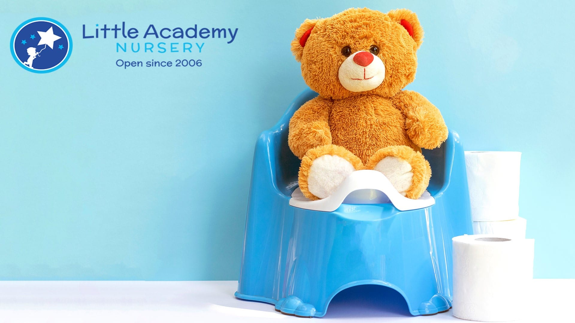 A small brown color teddy bear is sitting on a blue pot.