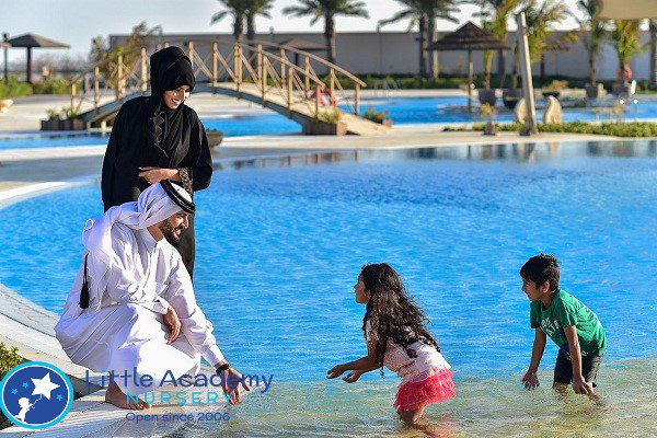 Two kids doing activity with their parents in a pool.