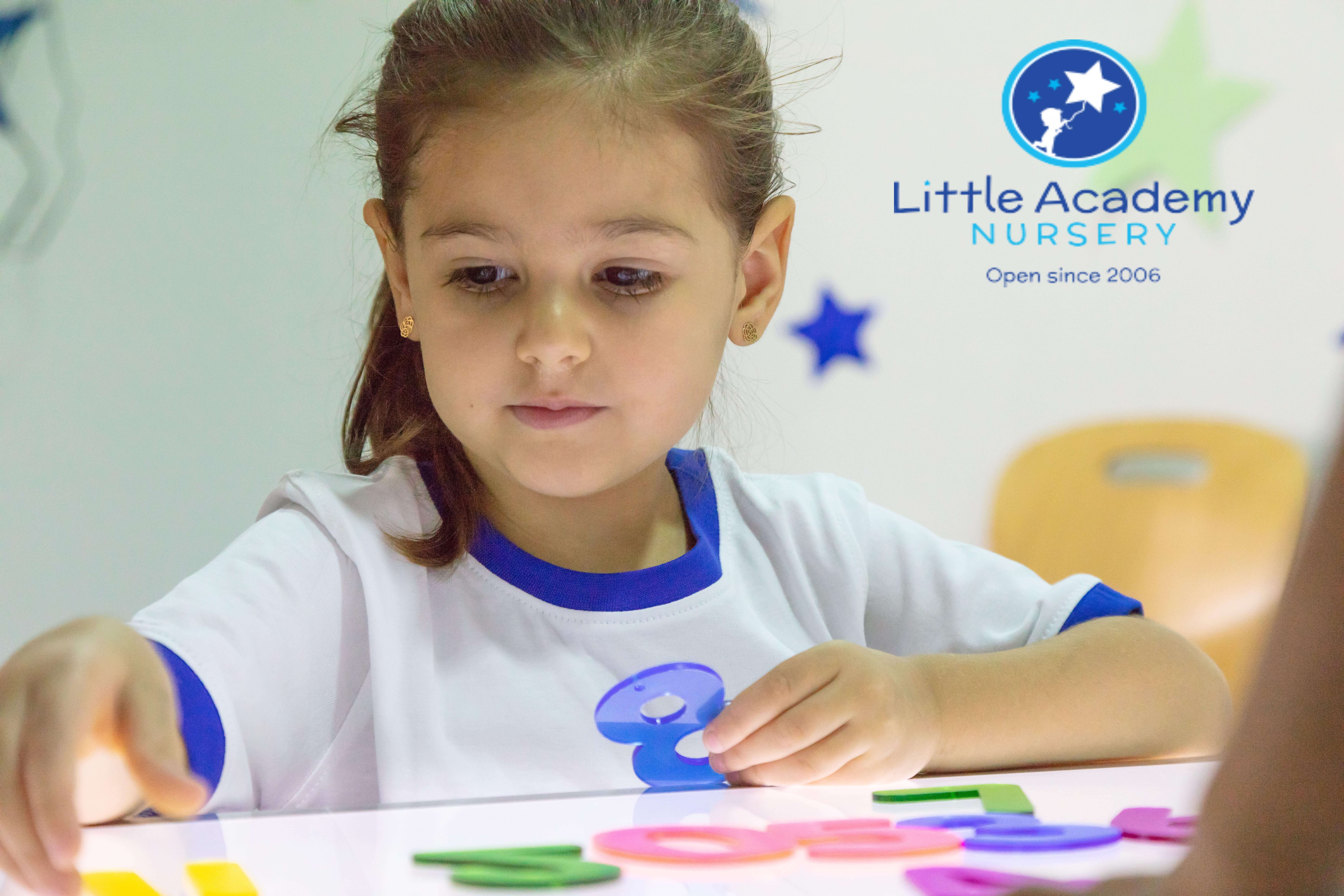 A little girl wearing a white and blue school uniform is sitting and playing with colorful toys.